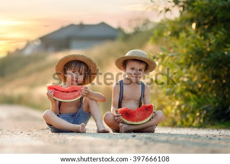 Two cute little boys, eating watermelon on a rural village path, summertime - stock photo