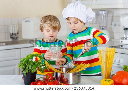 Two cute little brothers cooking italian meal with spaghetti and fresh vegetables in domestic kitchen. Sibling children in colorful shirts. - stock photo