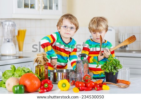 Two cute little brothers cooking italian soup and meal with fresh vegetables in home's white kitchen. Sibling children in colorful shirts. - stock photo