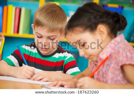 Two cute little children drawing at kindergarten - stock photo