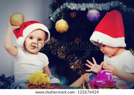 Two cute little girl sitting with gifts under the Christmas tree - stock photo