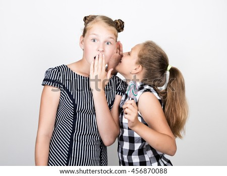 Two cute little girlfriend eating bright lollipops. Funny kids. Best friends pamper and posing. one of them whispers secret in the ear - stock photo