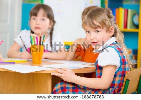 Two cute little girls drawing at kindergarten