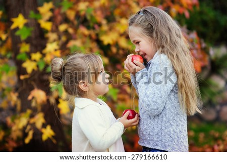 Two cute little girls eating red apple outside at beautiful autumn background - stock photo