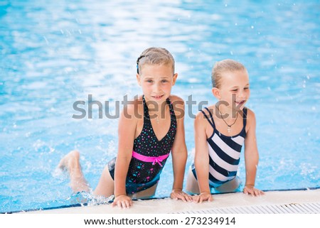 Two cute little girls in swimming pool posing - stock photo