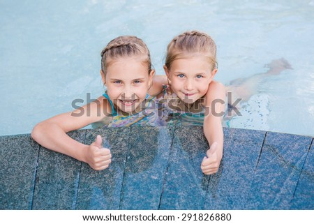 Two cute little girls in swimming pool with thumbs up - stock photo