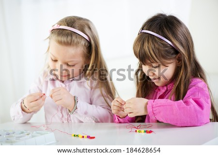 Two Cute little girls making bead Jewelry at home. - stock photo