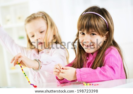 Two cute little girls Making bead jewelry at home  - stock photo