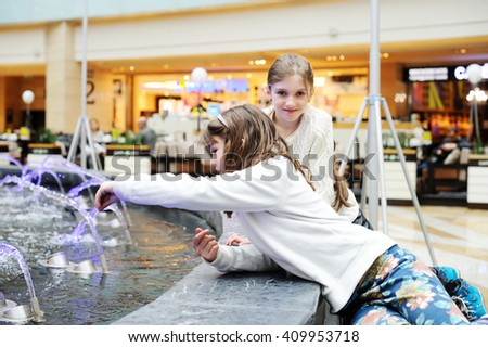 Two cute little girls playing with a city fountain on the market street