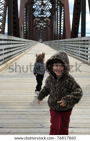 Two cute little girls running towards the camera laughing and playing on a wooden bridge - stock photo