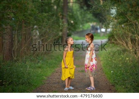 Two cute little girls talking emotionally standing in a Park.