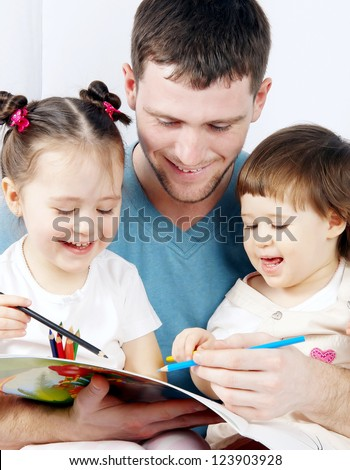 two cute little girls with their dad paint crayons - stock photo