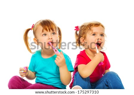 Two cute little girls with toothbrush isolated on white - stock photo