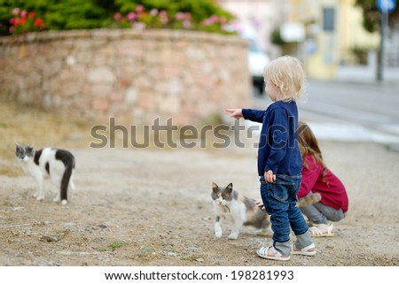 Two cute little sisters and a cat outdoors