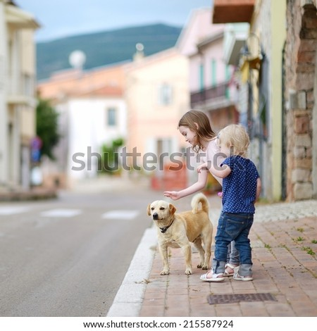 Two cute little sisters and a dog outdoors - stock photo