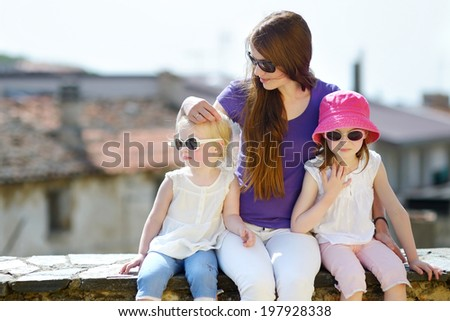 Two cute little sisters and their mother outdoors