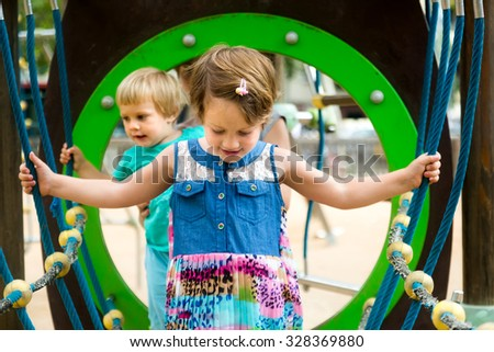 Two cute little sisters at action-oriented playground in park