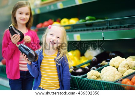 Two cute little sisters choosing fresh eggplants in a food store or a supermarket - stock photo