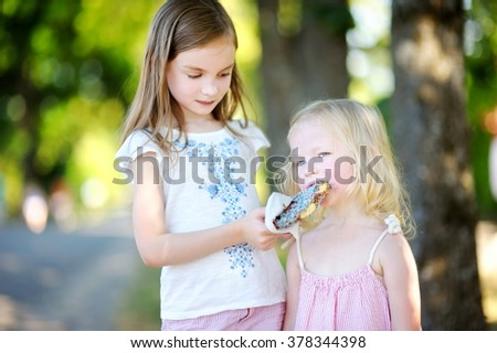 Two cute little sisters eating belgian waffle on a stick outdoors on warm summer day - stock photo