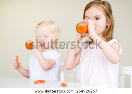 Two cute little sisters eating carrots and drinking carrot juice