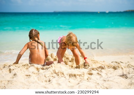 Two cute little sisters girls having fun on colorful tropical beach with turquoise water of ocean and white sand - stock photo