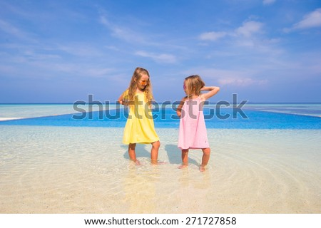 Two cute little sisters have fun together near swimming pool - stock photo