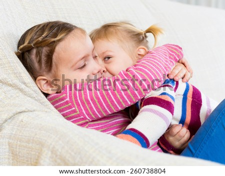 Two cute little sisters hugging on sofa at home - stock photo