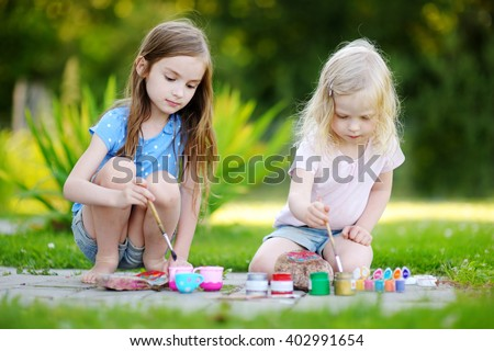 Two cute little sisters painting on stones together on hot summer day