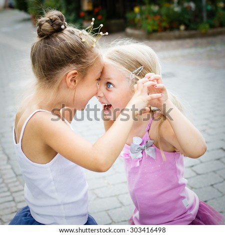 two cute little sisters, selective focus. The girl with dark hair is wearing a princess crown. - stock photo