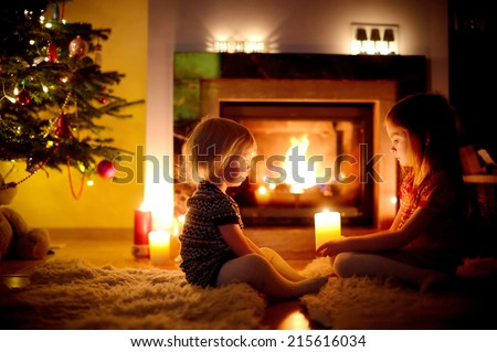Two cute little sisters sitting by a fireplace holding candles in a cozy dark living room on Christmas eve - stock photo