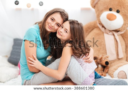 Two cute lovely sisters sitting and hugging in children room  - stock photo