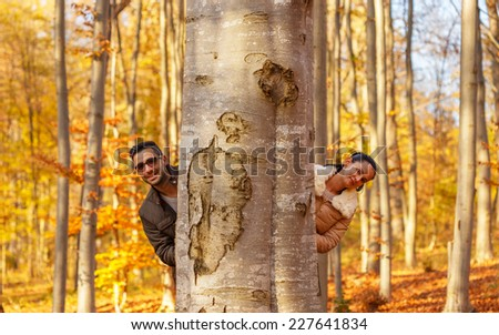 Two cute lovers smiling behind a tree while autumn season