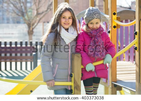Two cute positive preschooler age girls at urban playground