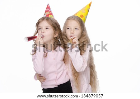 two cute preschool girls with party whistles on a white background