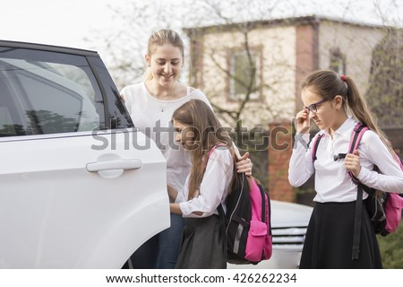 Two cute schoolgirls getting in the car to ride to school - stock photo