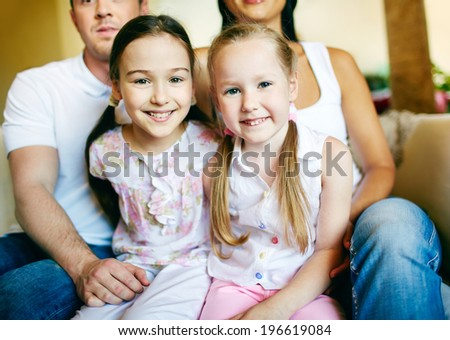 Two cute siblings looking at camera with their parents on background