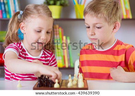 Two cute siblings playing chess at home - stock photo
