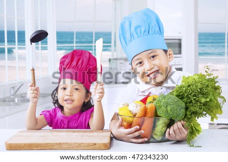 Two cute siblings preparing healthy food with fresh vegetables in the kitchen