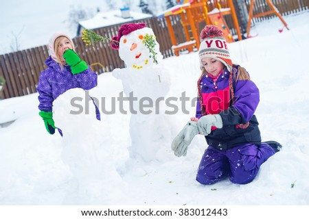 Two cute sister girls play in winter with snow man outside on backyard of village country house