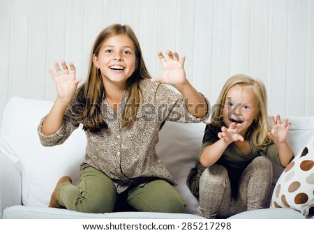 two cute sisters at home playing, little girl in interior - stock photo