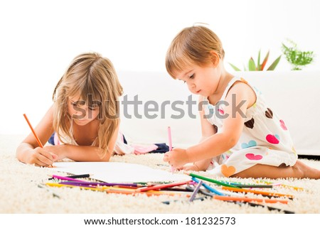Two Cute sisters drawing with color crayons on the carpet