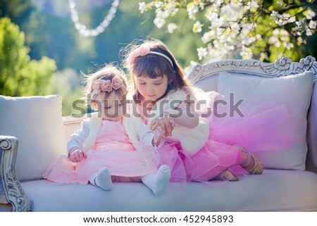 Two cute sisters in spring blossom garden