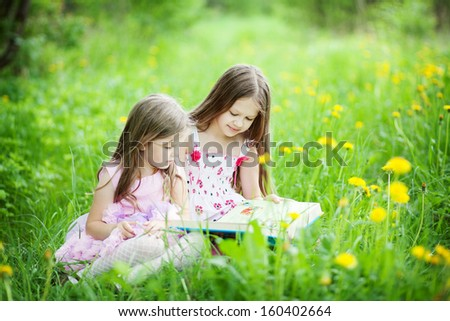 two cute sisters in the meadow reading a book - stock photo