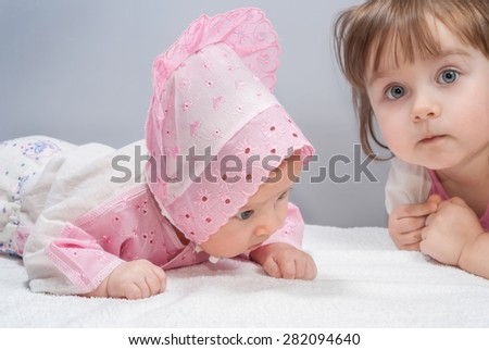 Two cute sisters, little senior girl and junior baby, family children - stock photo