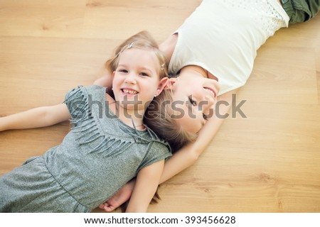 Two cute sisters on floor of children room smiling and having fun together - stock photo