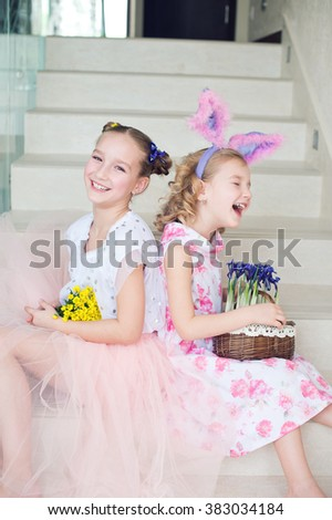 Two cute sisters sitting indoors with bunny ears, flowers and ginger bread, having fun celebrate Easter spring holiday together - stock photo