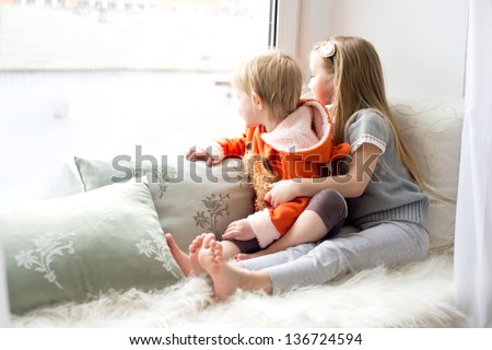 Two cute sisters sitting near window close to each other and playing - stock photo