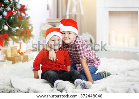 Two cute small brothers hugging on Christmas tree background - stock photo