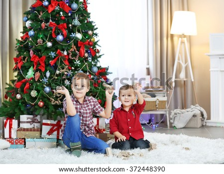 Two cute small brothers playing with wooden toys on Christmas tree background - stock photo