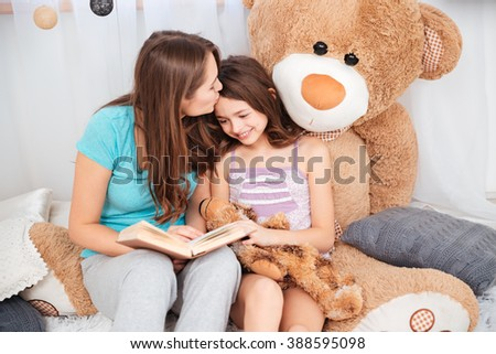 Two cute smiling sisters reading and kissing in children room - stock photo